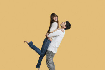 Happy young man carrying girlfriend over colored background