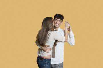 Portrait of young man hugging girlfriend over colored background