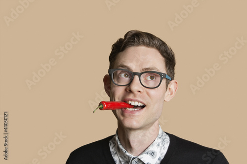 Mid adult man with red chili pepper while looking away over colored background