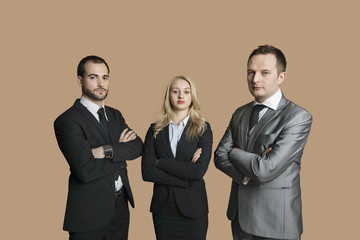 Portrait of young business people with arms crossed over colored background