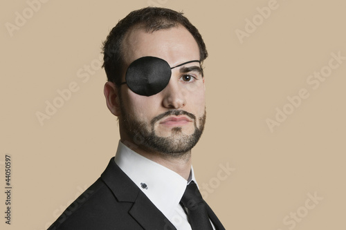 Portrait of a young businessman with eye patch over colored background