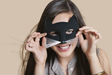 Portrait of a young woman imitating as cat while looking through eye mask over colored background
