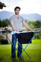 Mann hängt Wäsche im Garten auf