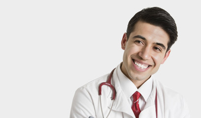 Cheerful Indian male doctor looking sideways over light gray background