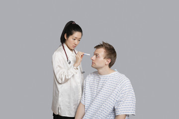 Doctor examining patient's eye with flashlight