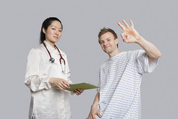 Portrait of patient gesturing okay with doctor holding a clipboard