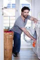 Mann entleert oder befüllt Waschmaschine