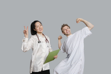 Portrait of doctor gesturing peace sign with patient cheering up