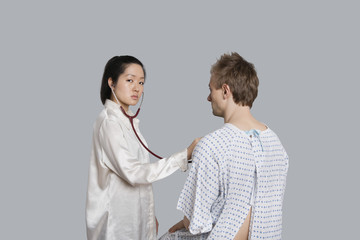 Portrait of a young female doctor examining male patient