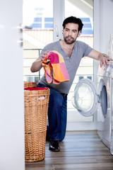 Mann füllt Wäsche in die Waschmaschine