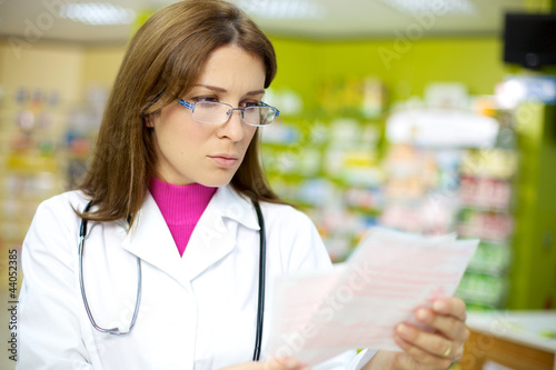 Female doctor reading prescription in pharmacy