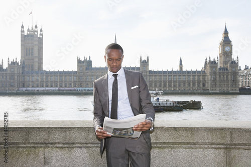 African American businessman reading newspaper with building in background