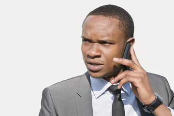 African American businessman looking away while talking on cell phone