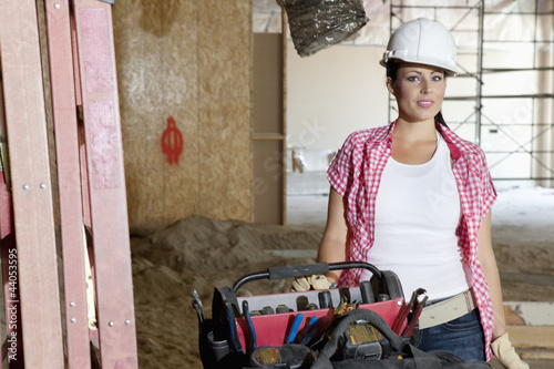Portrait of young architect wearing hardhat standing with toolbox