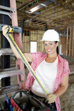 Portrait of happy female contractor with measuring tape at construction site