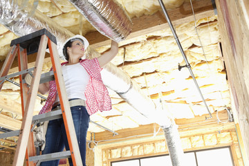 Low angle view of female worker working on incomplete ceiling