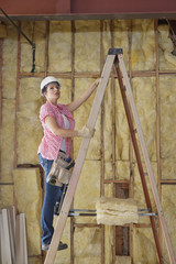 Female contractor climbing up the ladder at construction site