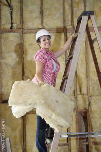 Portrait of a happy female construction worker carrying sponge while climbing ladder