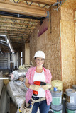 Portrait of a happy young woman with drill at construction site