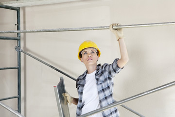 Mid adult female architect looking up while standing under scaffold at construction site