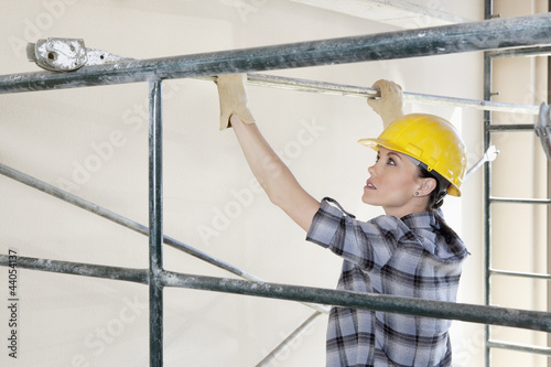 Back view of female contractor placing iron rod on scaffold