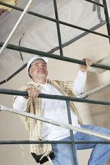 Front view of mature man climbing scaffold