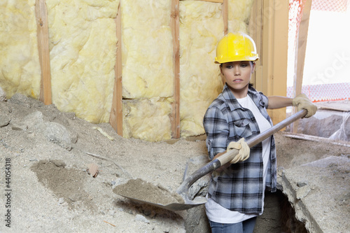 Female contractor digging sand at construction site