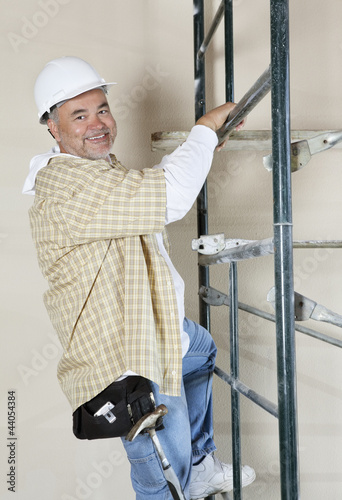 Portrait of a happy worker climbing scaffold