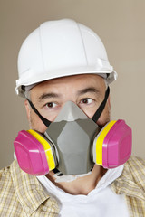 Close-up portrait of contractor with dust mask over colored background