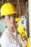 Serious female construction worker cutting wood with a power saw