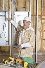 Portrait of a mature male construction worker checking electric meters at construction site