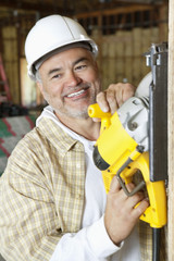 Happy mature male construction worker cutting wood with a circular saw