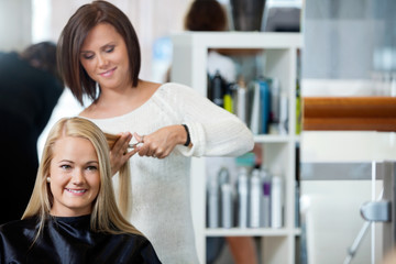 Woman Getting Haircut At Parlor