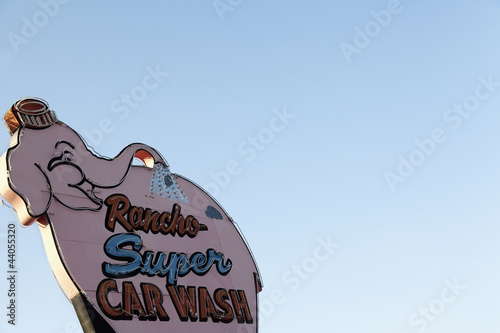 Car wash sign board over clear sky