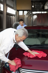 mature owner and young employee wiping vehicle with cloth in car wash