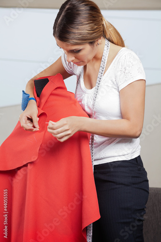 Fashion Designer Adjusting Pins On Fabric