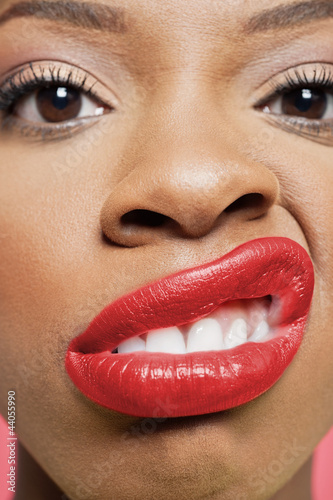 Close-up portrait of young woman with red lips grimacing