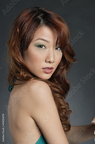 Sexy young Chinese woman over colored background