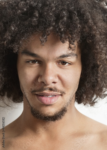 Portrait of a trendy young man with curly hair over white background