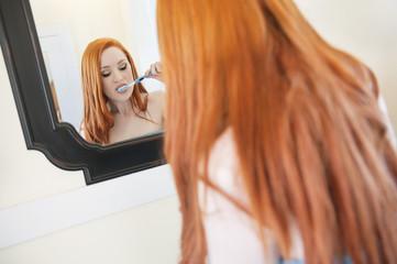 Young woman brushing teeth bathroom