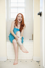 Portrait of a young woman in bathroom applying cream on legs