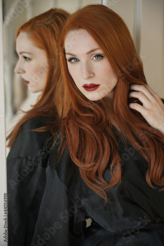 Portrait of a beautiful young woman in robe with hand in hair