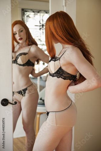 Beautiful young woman adjusting her lingerie in front of mirror