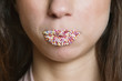 Cropped image of candy sprinkled lips woman