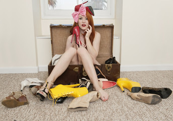 Portrait of young woman sitting in suitcase with footwear lying on floor