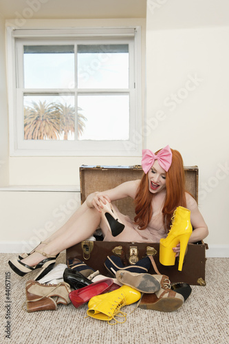 Happy woman sitting in suitcase with footwear lying on floor