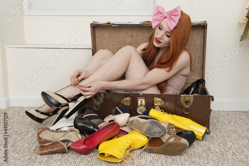 Young woman with bow headband tying footwear while sitting in suitcase