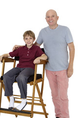 Portrait of senior man with pre-teen boy sitting on director's chair over white background