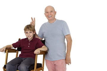 Portrait of senior man gesturing peace sign while pre-teen boy sitting on director's chair over white background