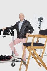 Full length portrait of a happy senior photographer with equipments in studio